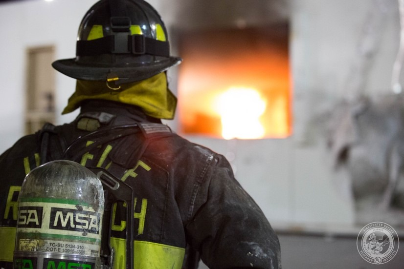 UL FSRI Research Engineer dressed in firefighter personal protective equipment (PPE) observes live-fire experiment