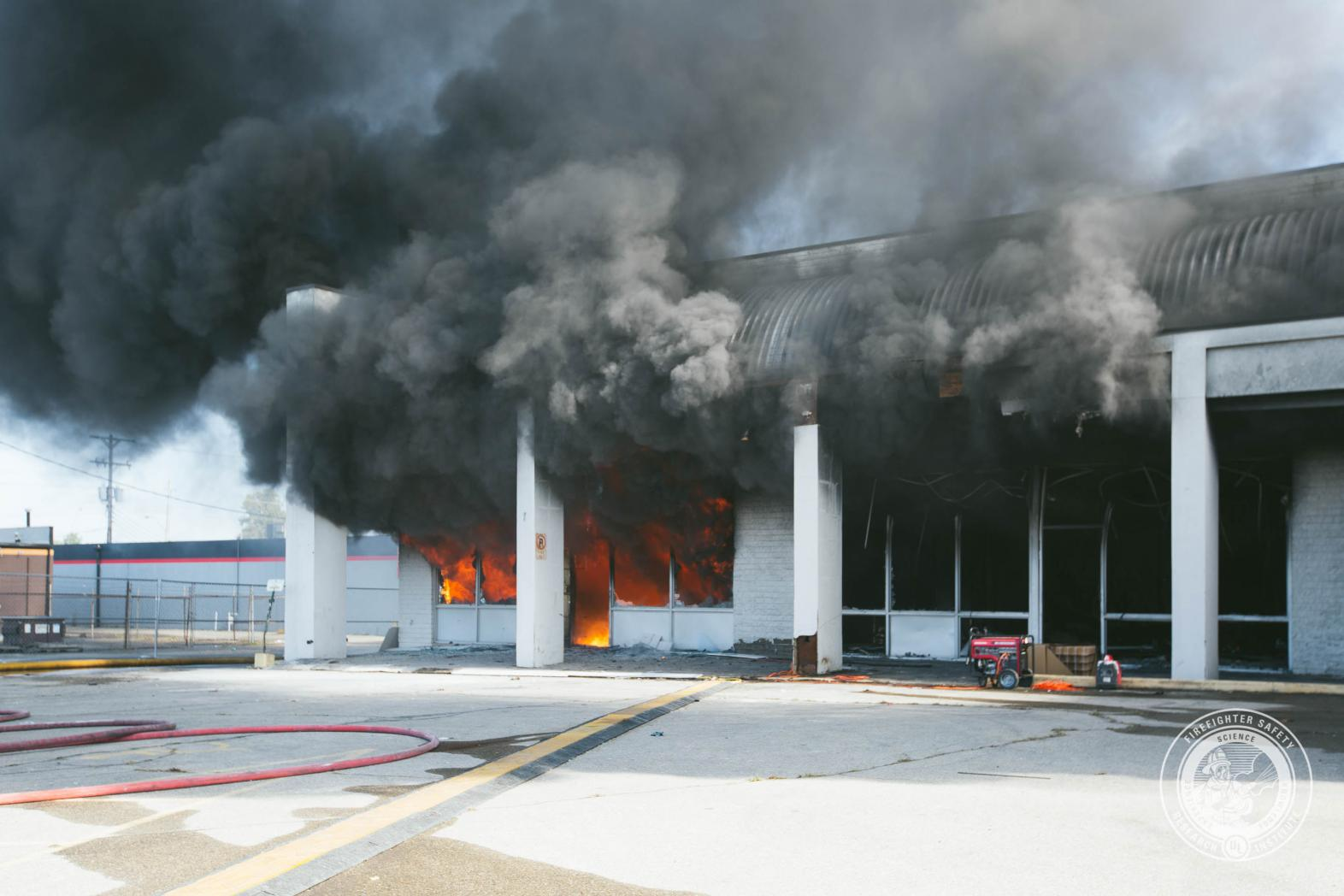 Commercial strip mall front with smoke and flames showing from the windows