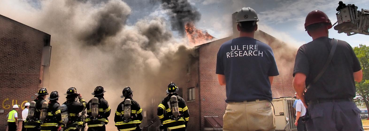 firefighters and UL researchers standing in front of a building on fire