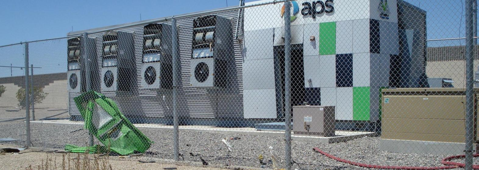 Energy storage system with walls bowed out and broken fence with the door to system leaning on fence after an explosion