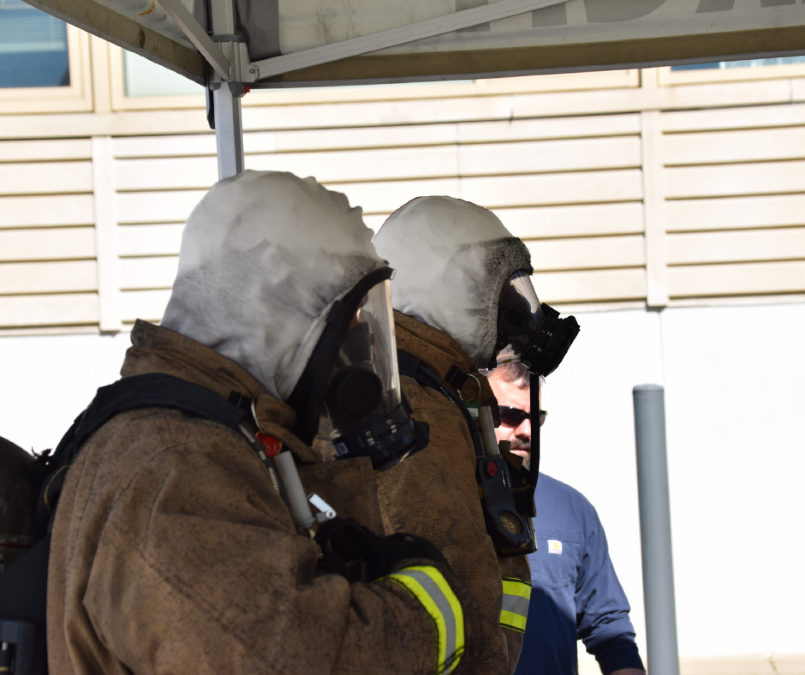 firefighters wearing protective gear and white hoods