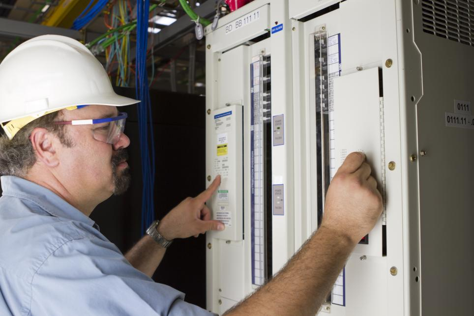 A male electrician inspects and electrical control panel.
