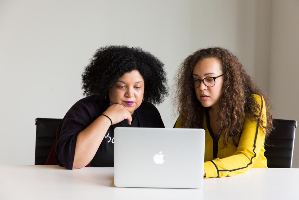 Two women sitting at a laptop computer