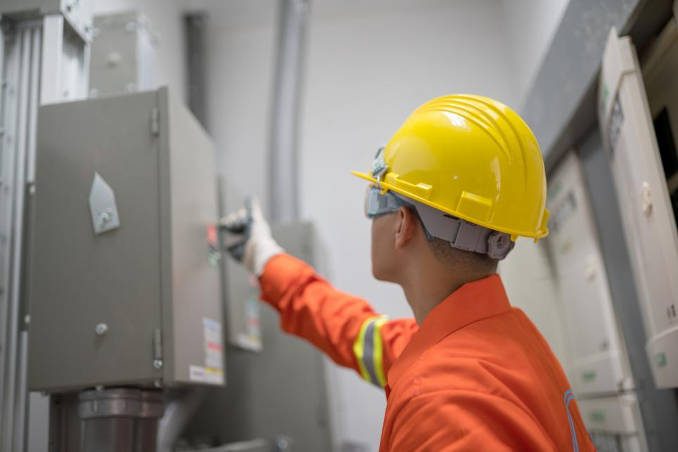 Technician reviews safety information on electrical panel