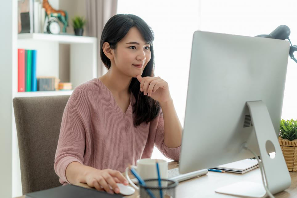 businesswoman using computer to work from home and participate in virtual meeting